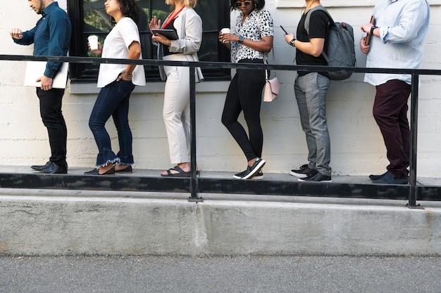 Uomini d'affari che tengono in mano dispositivi digitali mentre aspettano in fila