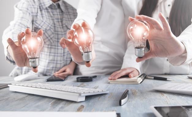 Gente di affari che tiene lampadina. idea. lavoro di squadra