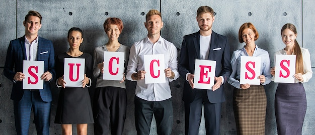 Gente di affari che tiene lettere di successo stampate su carta