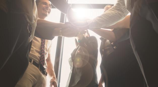 Gli uomini d'affari si uniscono e impilano mano insieme durante il loro incontro di lavoro con il sole r