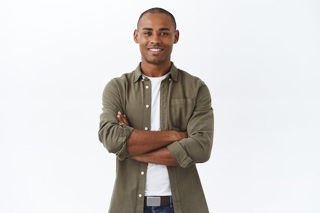 Concetto di affari, persone e stile di vita. ritratto di un bell'uomo afroamericano incrocia le mani sul petto e sorride compiaciuto
