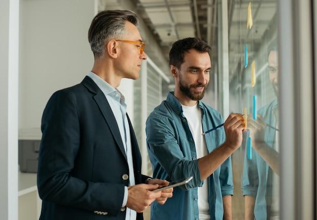 Gli uomini d'affari che pianificano le riunioni iniziano utilizzando le note adesive che lavorano in ufficio