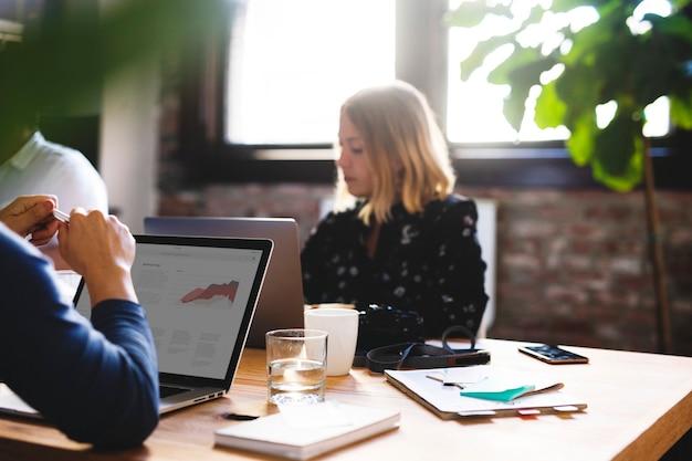 Uomini d'affari in una sala riunioni che utilizzano un laptop Foto Premium