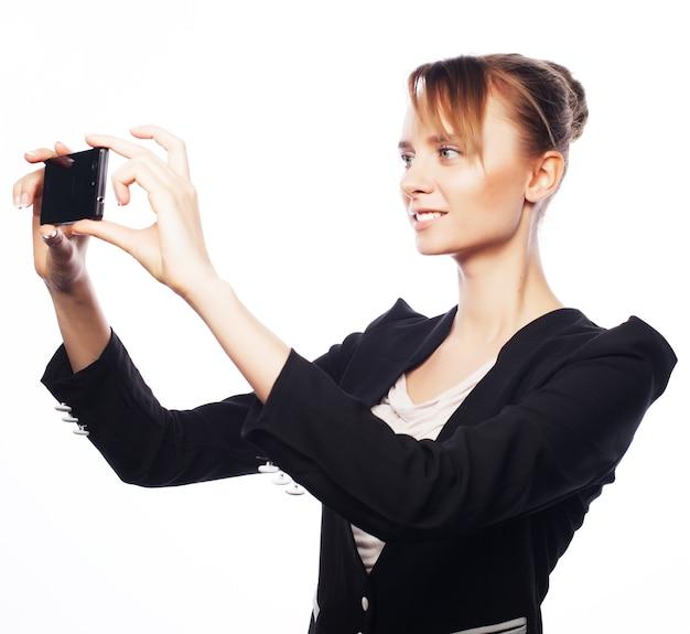 Concetto di affari, persone e ufficio: giovane donna d'affari con il telefono cellulare. emozione positiva isolato su bianco.