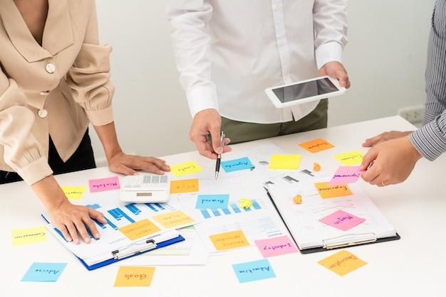Gente di affari che pianifica il progetto di avvio inserendo una sessione di note adesive per condividere l'idea sulla parete di vetro, concetto di ufficio di analisi strategica