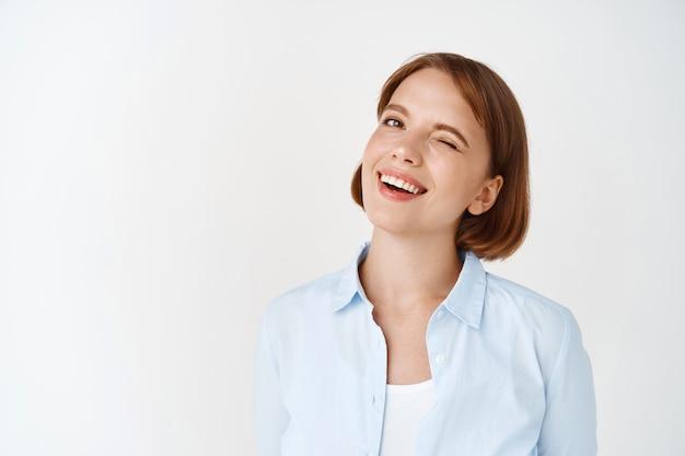 Uomini d'affari. ritratto di giovane donna con i capelli corti, ammiccante e sorridente motivata, in piedi ottimista sul muro bianco