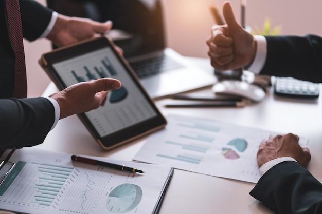 Gli uomini d'affari riportano le vendite al capo, il concetto finanziario e contabile, il lavoro di squadra collaborativo.