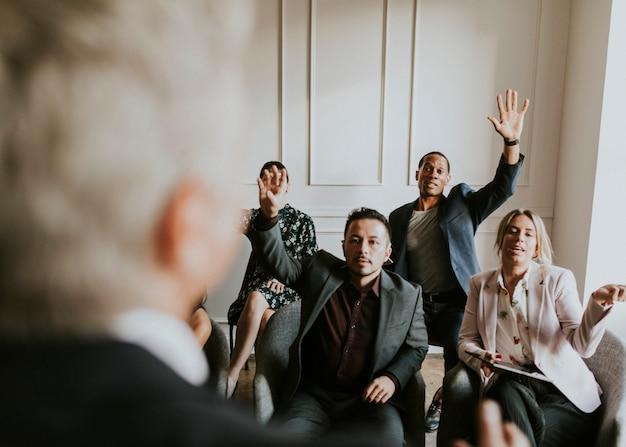 Uomini d'affari in un seminario che alzano la mano