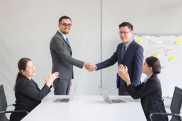 Gli uomini d'affari si stringono la mano dopo aver raggiunto un accordo commerciale con una segretaria seduta e applaudendo per congratularsi con la sala riunioni