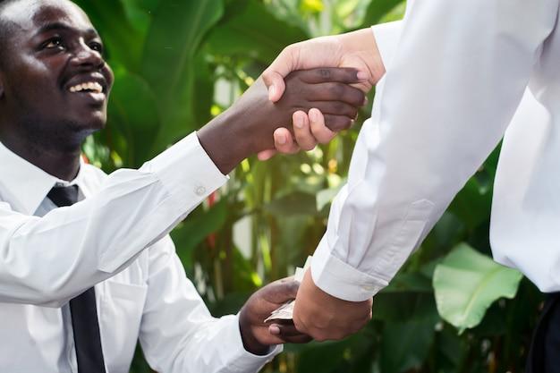 Gente di affari che stringe le mani dopo la firma del contratto alla caffetteria