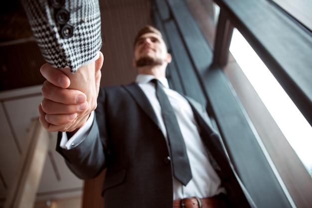 Uomini d'affari si stringono la mano, terminando una riunione.
