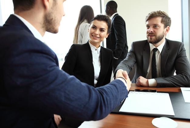 Uomini d'affari che si stringono la mano, finendo una riunione