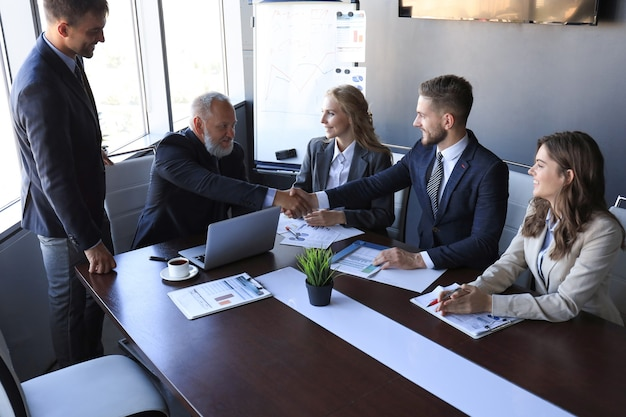 Uomini d'affari che si stringono la mano, finendo una riunione.