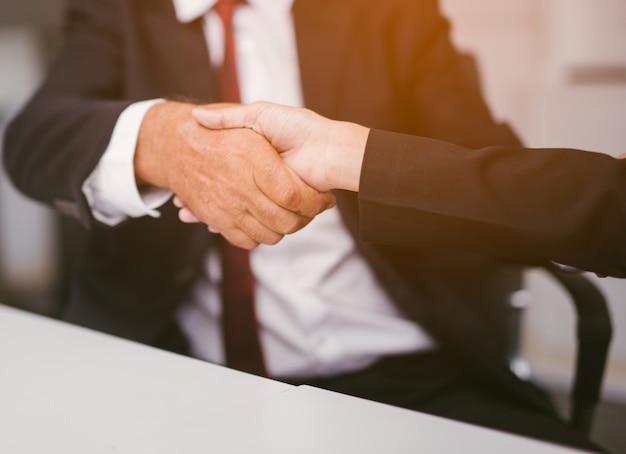 Uomini d'affari si stringono la mano in ufficio.