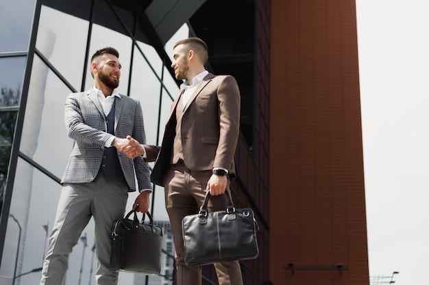 La gente di affari si stringono la mano al di fuori del moderno edificio per uffici