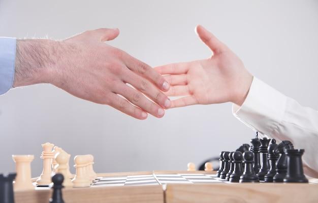 La gente di affari si stringono la mano. giocare a scacchi