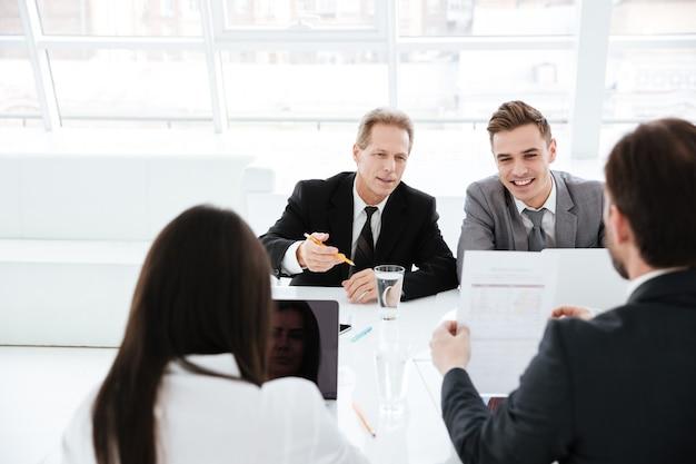 Gli uomini d'affari si siedono al tavolo nella sala conferenze