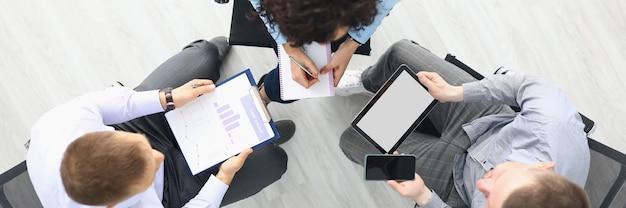 Gli uomini d'affari si siedono su sedie con tablet e grafici commerciali e discutono i piani di lavoro top ...