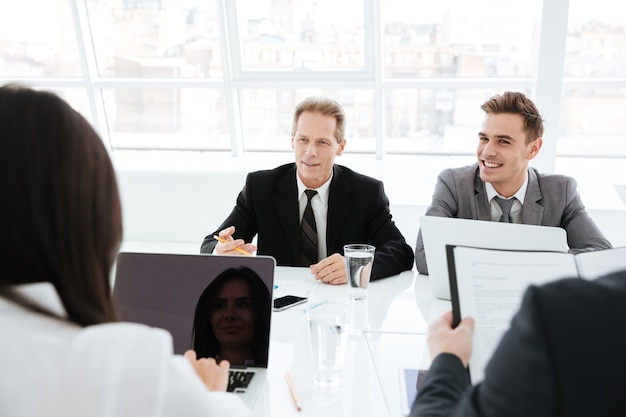Uomini d'affari seduti al tavolo e che interagiscono in una riunione nella sala conferenze