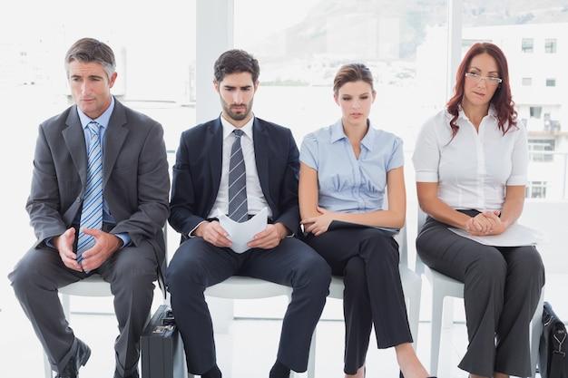 Uomini d'affari seduti in fila