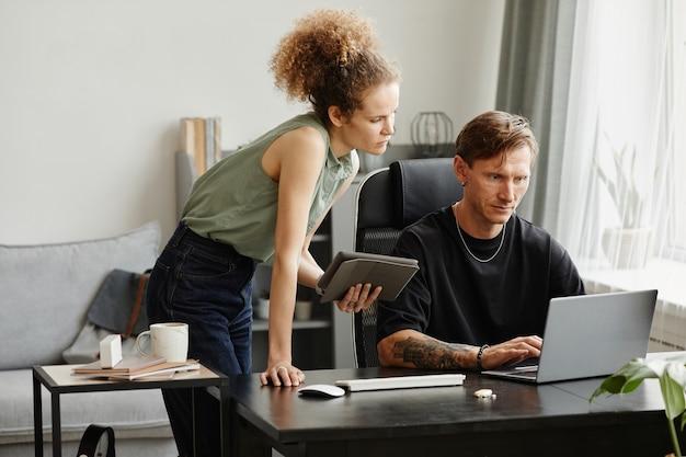 Gli uomini d'affari seduti al tavolo e lavorando al computer discutono di nuovi software in team in ufficio