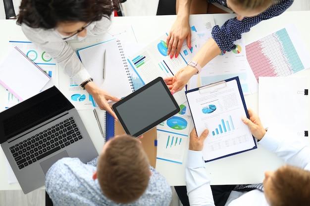 Gli uomini d'affari stanno intorno al tavolo su cui giacciono i laptop tablet grafici commerciali