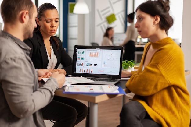 Uomini d'affari che parlano con il leader del team utilizzando appunti con documenti puntati su di esso, presentando idee finanziarie di avvio al manager, brainstorming sulla strategia di gestione del progetto nell'ufficio dell'azienda