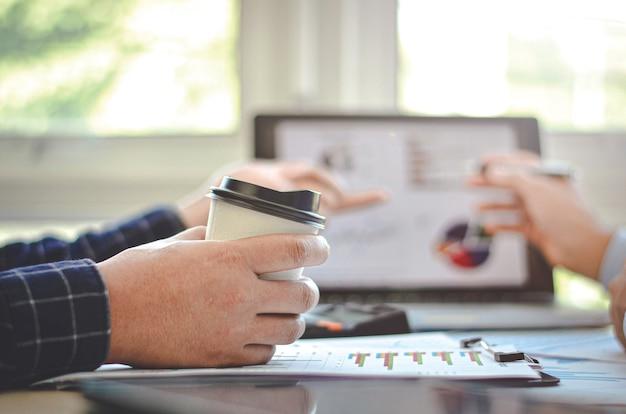 Gli uomini d'affari del team chattano per lavorare e bere caffè insieme in una caffetteria.