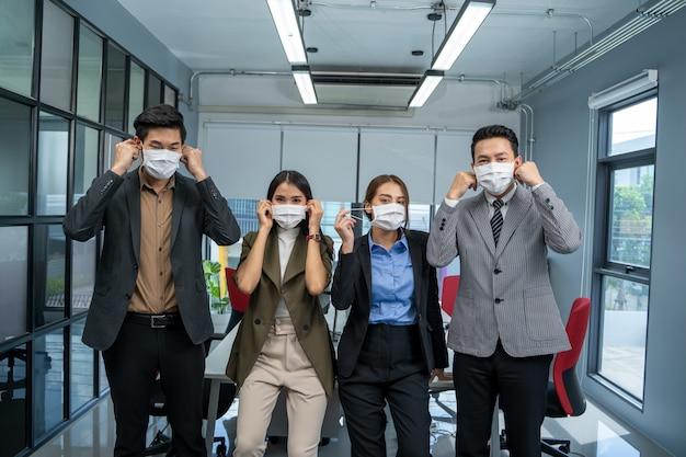 La gente di affari squadra che indossa la maschera per proteggere la malattia da virus corona che lavora insieme.