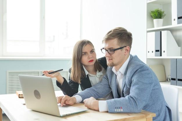 Uomini d'affari, lavoro di squadra e concetto di ufficio - donna e uomo stanno lavorando al progetto di avvio