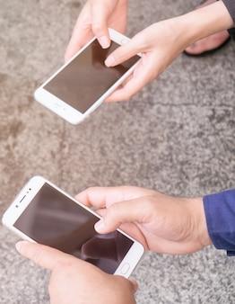 Gli uomini d'affari usano il cellulare per comunicare tra loro tramite l'e-mail di chat online di rete.
