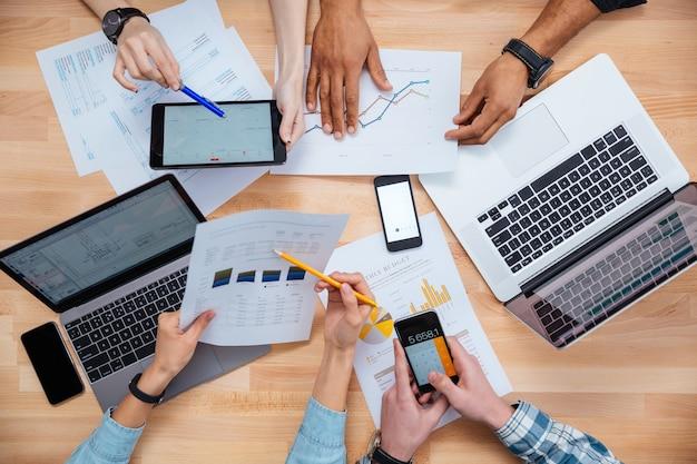 Uomini d'affari che utilizzano telefoni cellulari e laptop, calcolano e discutono grafici e diagrammi per rapporti finanziari