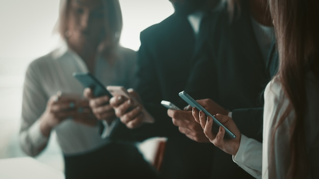 Uomini d'affari che utilizzano telefoni cellulari insieme in piedi in ufficio. immagine ravvicinata di mani umane che tengono smartphone. immagine sfocata. messa a fuoco selettiva sulla mano femminile in primo piano.