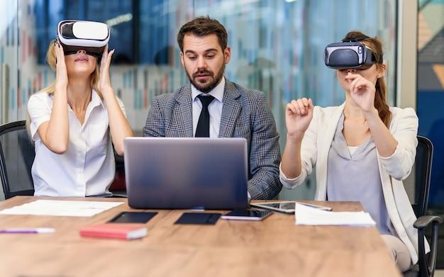 Uomini d'affari che utilizzano occhiali per realtà virtuale durante la riunione. team di sviluppatori che testano le cuffie da realtà virtuale e discutono di nuove idee per migliorare l'esperienza visiva.