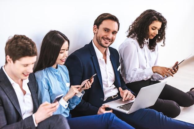 Gli uomini d'affari con gadget seduti sullo sfondo del muro bianco