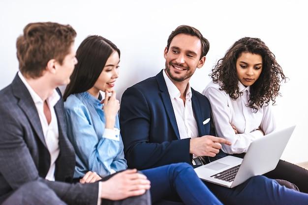 Gli uomini d'affari con un laptop seduto sullo sfondo del muro bianco