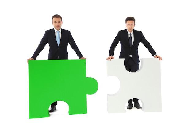 Gente di affari con i pezzi di puzzle isolati su fondo bianco, concetto di compatibilità di affari