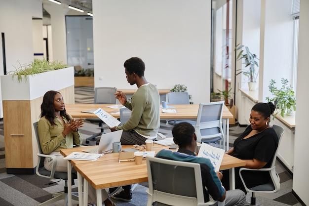 Uomini d'affari che lavorano in un ufficio open space e discutono di grafici e rapporti con varie vendite e...
