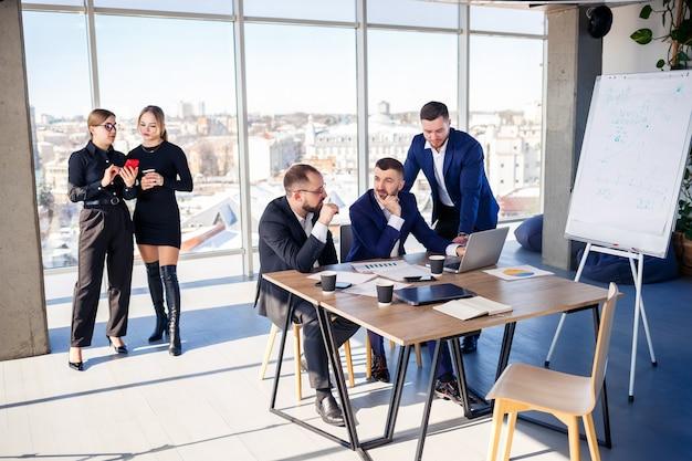 Uomini d'affari che lavorano insieme in un ufficio moderno con vista sul paesaggio urbano. il direttore racconta allo staff le nuove tecnologie. concetto di lavoro d'ufficio