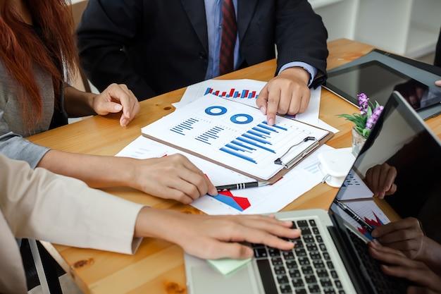 Gli uomini d'affari a lavorare con relazioni finanziarie e un computer portatile.