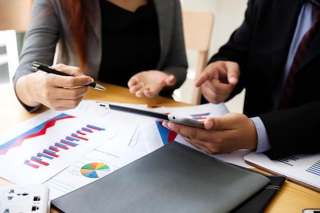 Gli uomini d'affari a lavorare con relazioni finanziarie e un tablet.