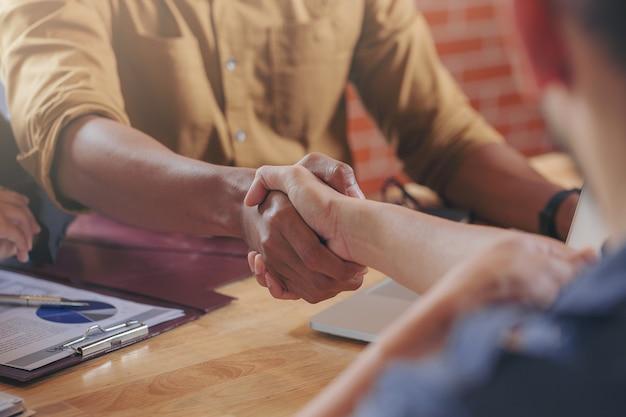 Gente di affari stretta di mano alla riunione di lavoro dopo la firma del contratto immobiliare con i partner commerciali messa a fuoco selezionata