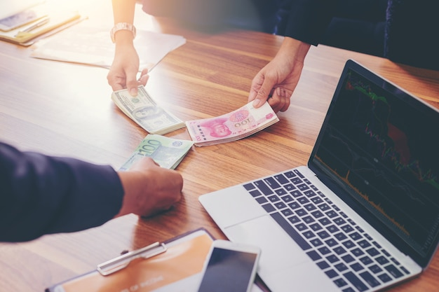 Gente di affari che tiene soldi che dividono per l'investimento di scambio