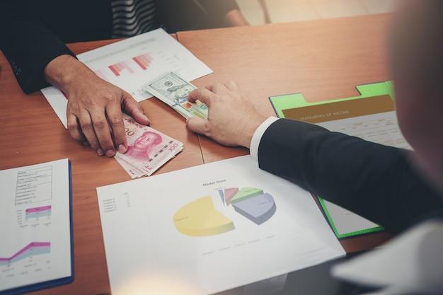 Uomini d'affari in possesso di dollari usd, yuan rmb per la condivisione di denaro per investimenti in cambi. guerra commerciale