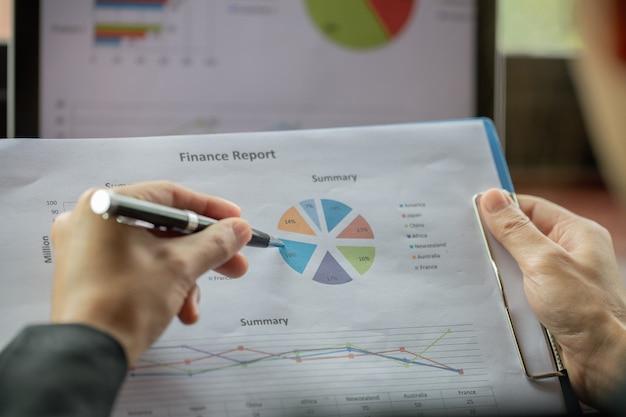 Uomo d'affari che analizza le statistiche finanziarie visualizzate su carta millimetrata