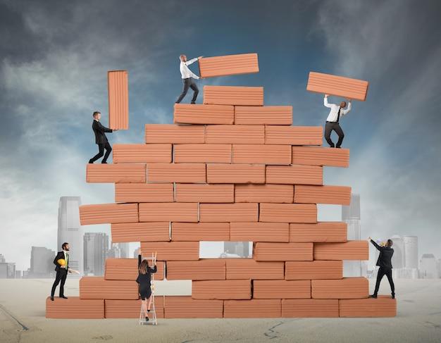 L'uomo d'affari ha costruito insieme un grande muro di mattoni