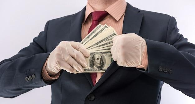 Persona d'affari mano in guanti protettivi blu con denaro isolato su sfondo bianco. salva il concetto di protezione covid 19 coronavirus