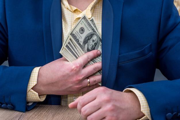 Persona di affari che nasconde le note del dollaro in tasca