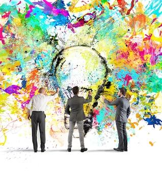 Persona di affari dipingere insieme una grande lampadina colorata sul muro