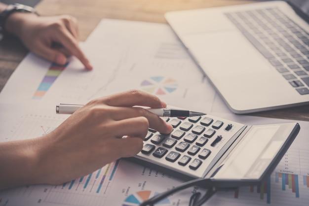 Uomo d'affari seduto alla scrivania di un ufficio utilizzando la calcolatrice per lavorare. analisi e pianificazione del concetto di business